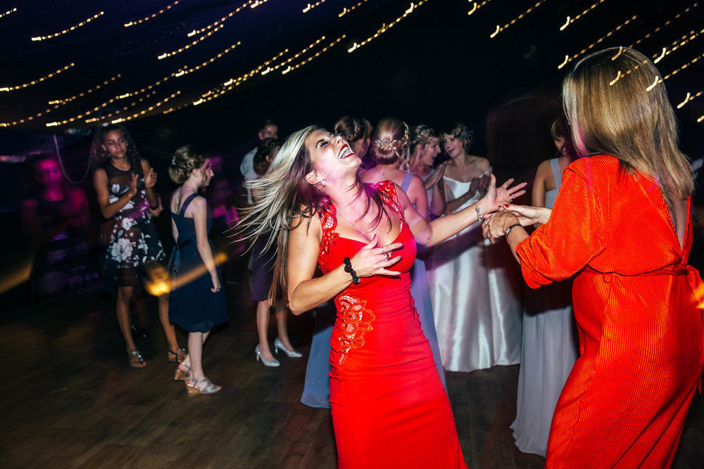 Wedding guest rocks out on dance floor at Hedingham Castle, Essex Documentary Wedding Photographer
