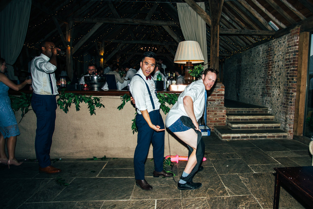 Groom points to ripped trousers of wedding guest at The Long Barn, Essex Documentary Wedding Photographer