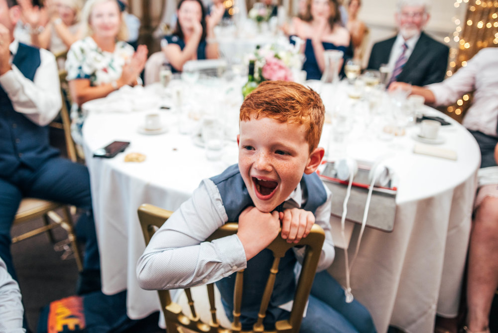 Page boy laughs during speeches at Blake Hall, Ongar, Essex Documentary Wedding Photographer