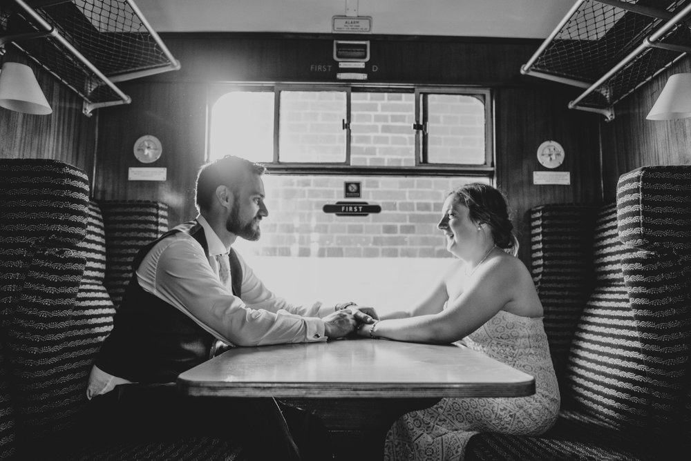 Bride and Groom hold hands on train at East Anglian Railway Museum, Essex Documentary Wedding Photographer