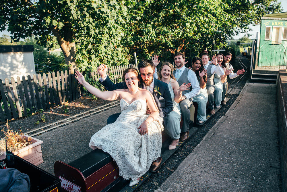 Bride, Groom and wedding guests ride train at East Anglian Railway Museum, Essex Documentary Wedding Photographer