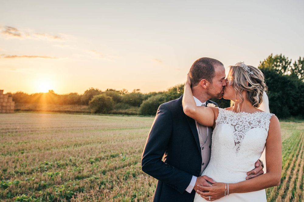 Bride and Groom kiss at sunset at Houchins Farm, Coggeshall, Essex Documentary Wedding Photographer