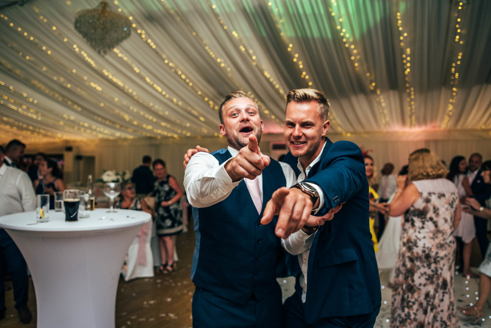wedding guests on dance floor laugh at camera Quendon Hall, Essex Documentary Wedding Photographer