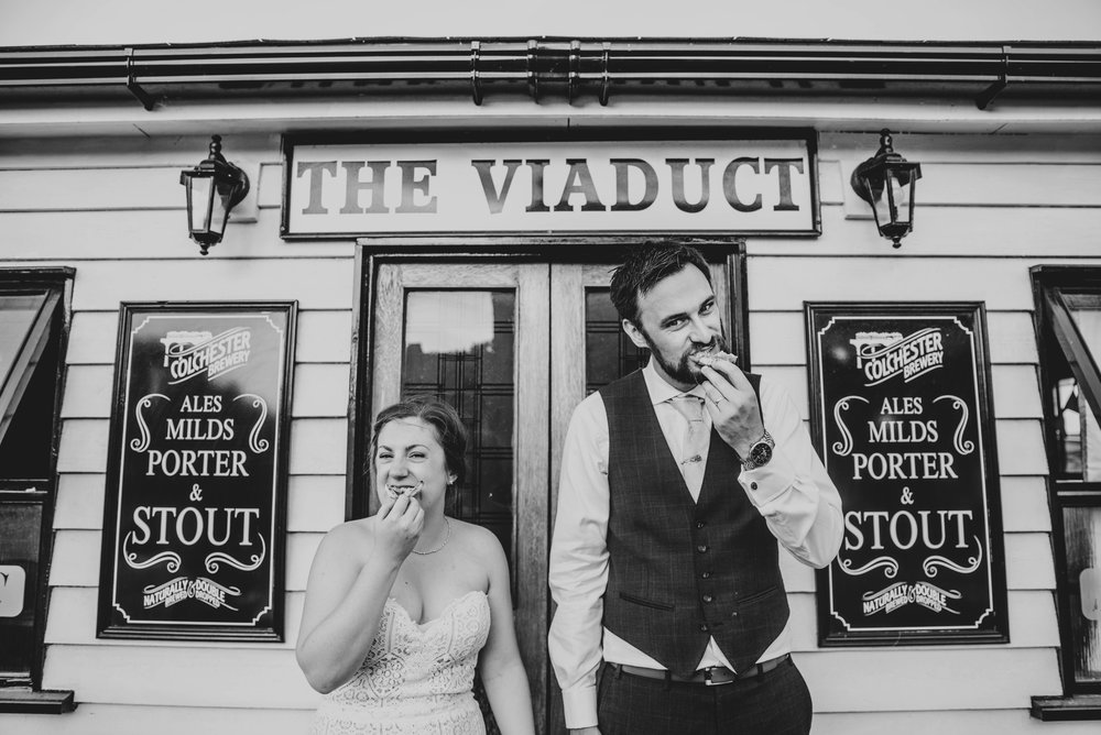 Bride and Groom eat pizza outside Viaduct Pub at East Anglian Railway Museum, Essex Documentary Wedding Photographer