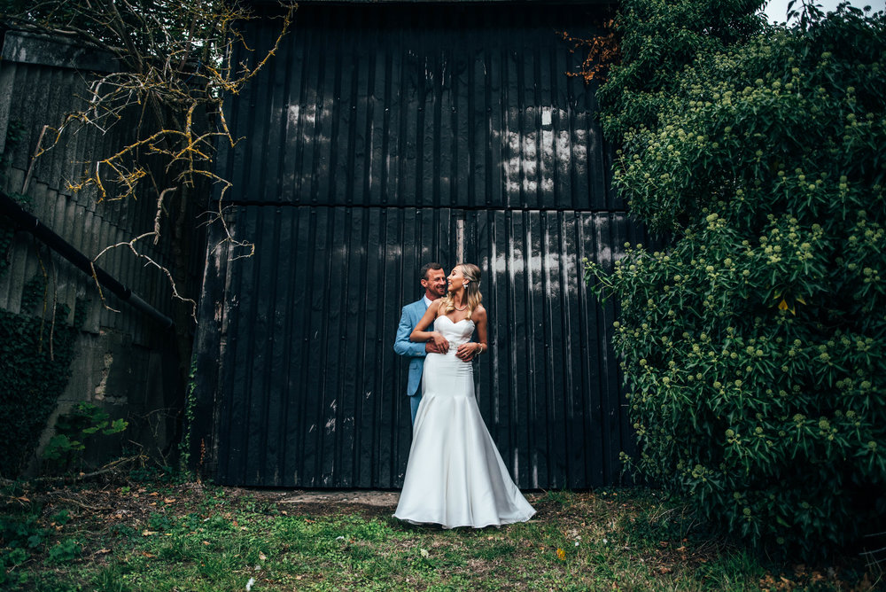 Bride and Groom outside barn at Fennes, Braintree, Essex Documentary Wedding Photographer