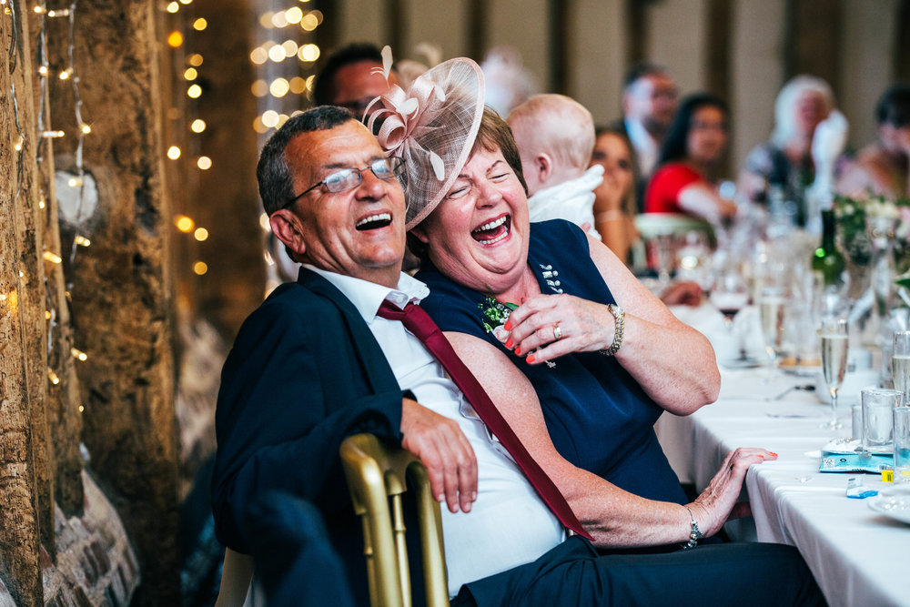 Parents of the Groom laugh at speeches at Blake Hall, Ongar, Essex Documentary Wedding Photographer