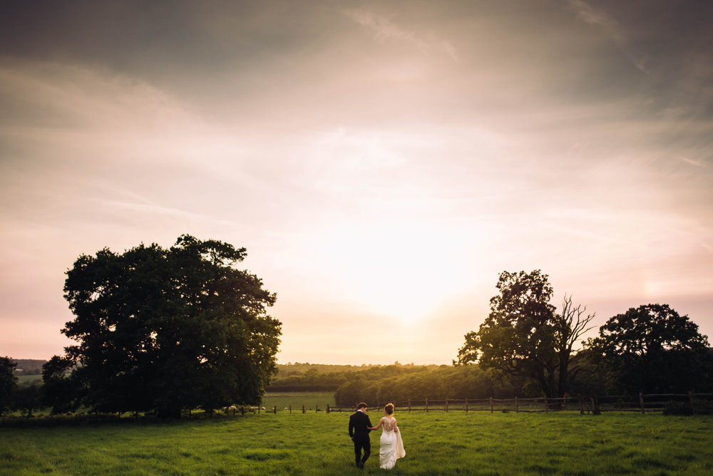 Bride and Groom walk in field at sunset at Gaynes Park, Epping, Essex Documentary Wedding Photographer