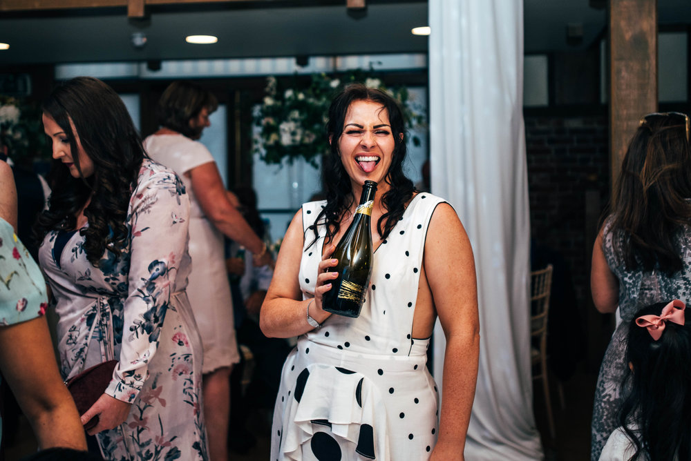 Tipsy wedding guests pokes out tongue and holds champagne bottle at Gaynes Park, Epping.  Essex Documentary Wedding Photographer