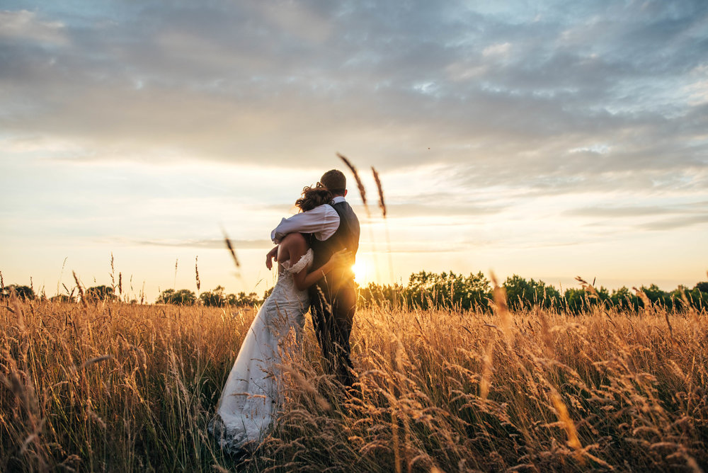 Bride and Groom in field at sunset at Stock Brook Manor, Billericay, Essex Documentary Wedding Photographer