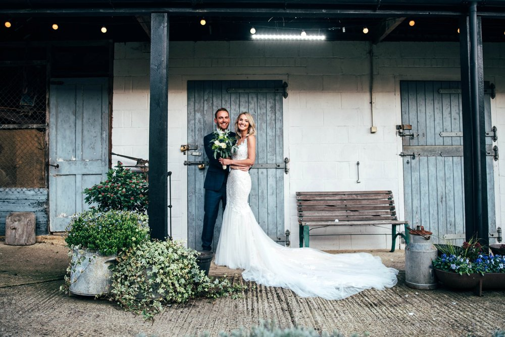 Nathalie & Kieron, an Autumn Barn Wedding at The Granary Estates with Champagne Golds, Greens and Fairy lights. Groom in Navy Check.