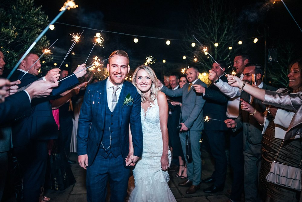 Nathalie & Kieron, an Autumn Barn Wedding at The Granary Estates with Champagne Golds, Greens and Fairy lights. Groom in Navy Check. Sparkler Exit