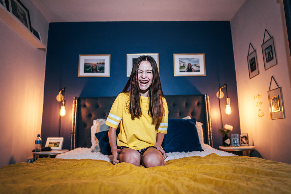 Tween girl on yellow bed. Essex Documentary Wedding and Family Portrait Photographer