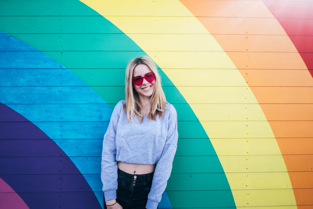 Teen girl in pink sunglasses stands against rainbow wall Southend Pier Essex Documentary Wedding & Portrait Photographer