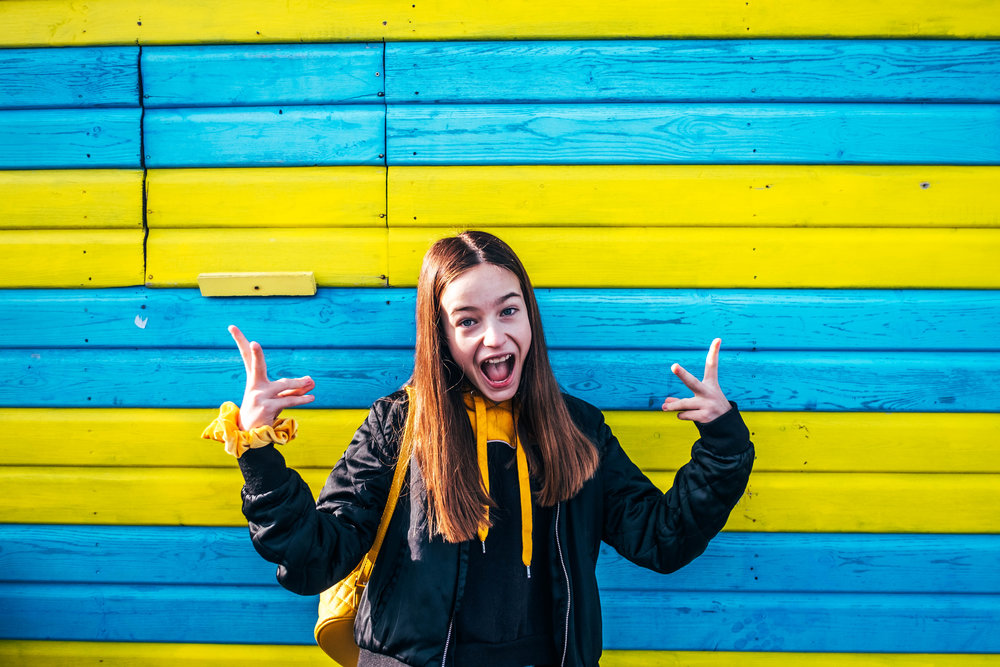 Tween girl smiles again Blue Yellow wall Southend Pier Essex Documentary & Wedding Photographer