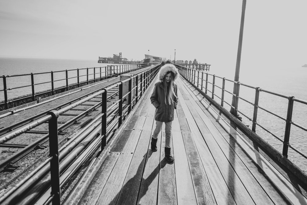 Little girl in hooded coat on Southend Pier Essex Documentary Wedding & Portrait Photographer
