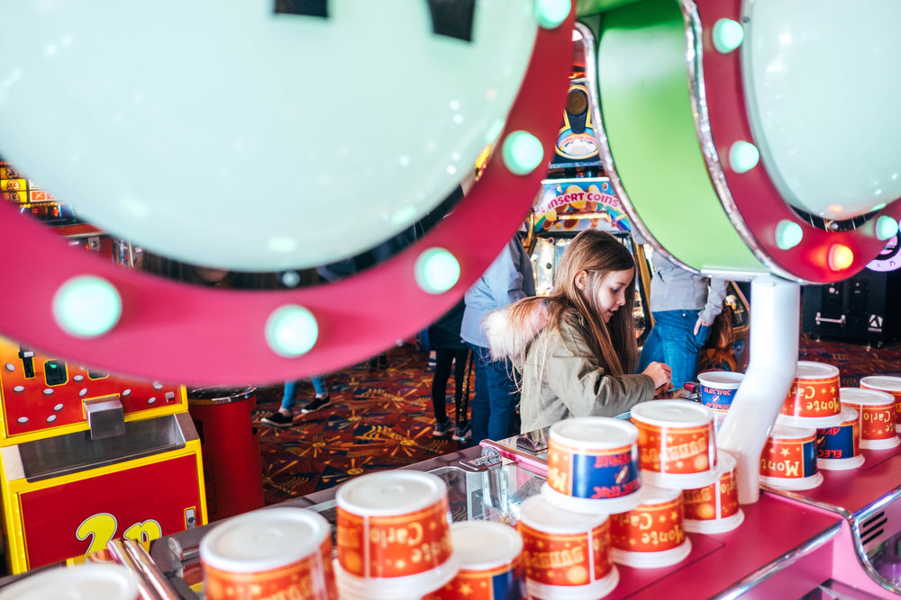 Little girl plays slot machines in arcade Essex Documentary Wedding & Portrait Photographer
