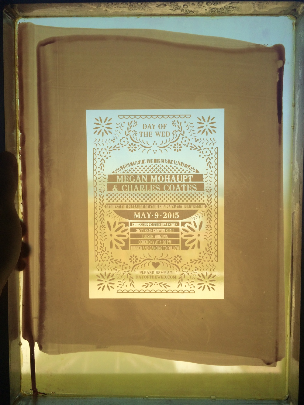 Our wedding design is photo-exposed onto a screen. This screen is the stencil that we push ink through and onto the paper below.