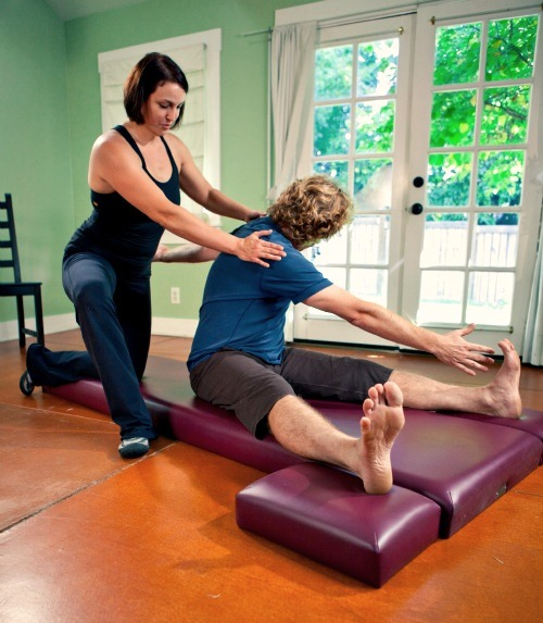 Paige helps a student with a Pilates mat exercise