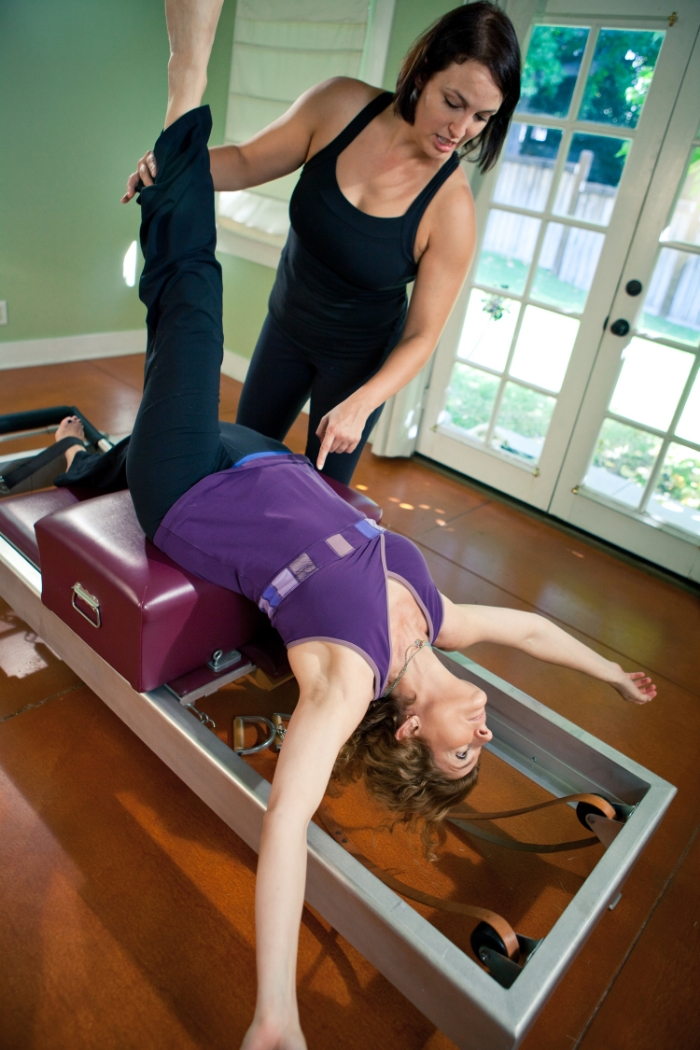 Paige helps a student with a Pilates Reformer exercise