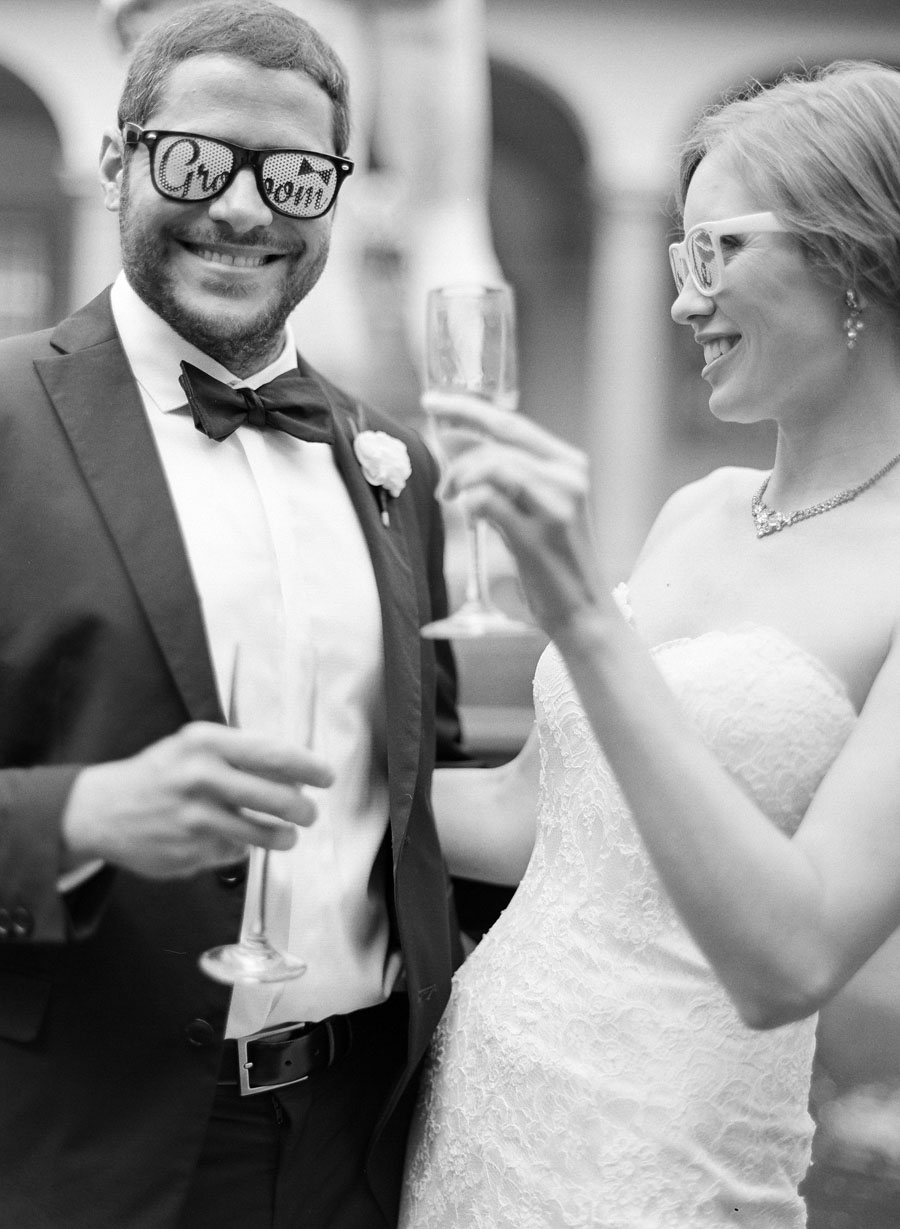 bride and groom toasting with playful sunglasses