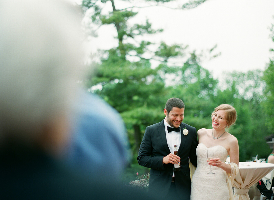 bride and groom laughing during speeches during outdoor wedding at villa terrace