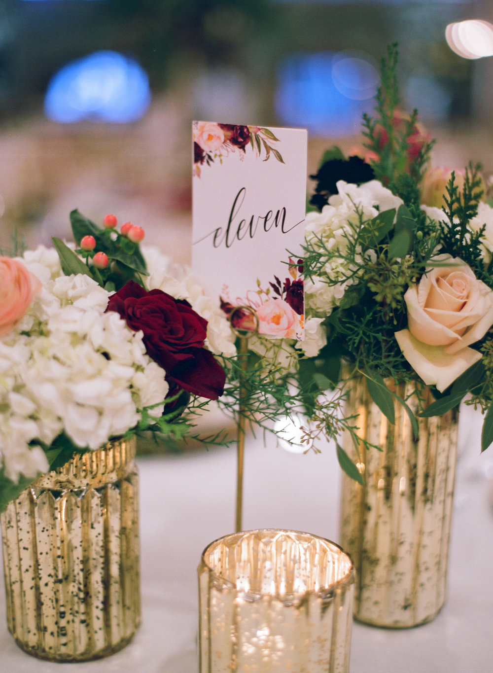 winter wedding reception table decor in burgundy and gold