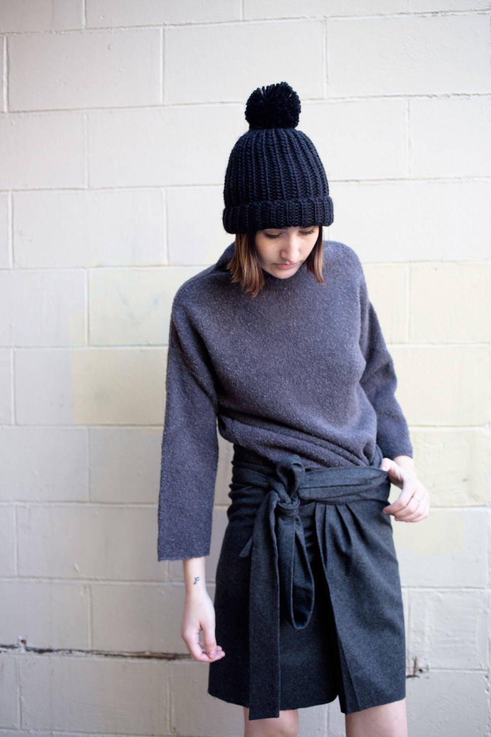Wearing Achro  High Neck Charcoal Sweater ,  Achro Wool Wrap Skirt,  and Pipe and Row Staples Oversized Pom Beanie.