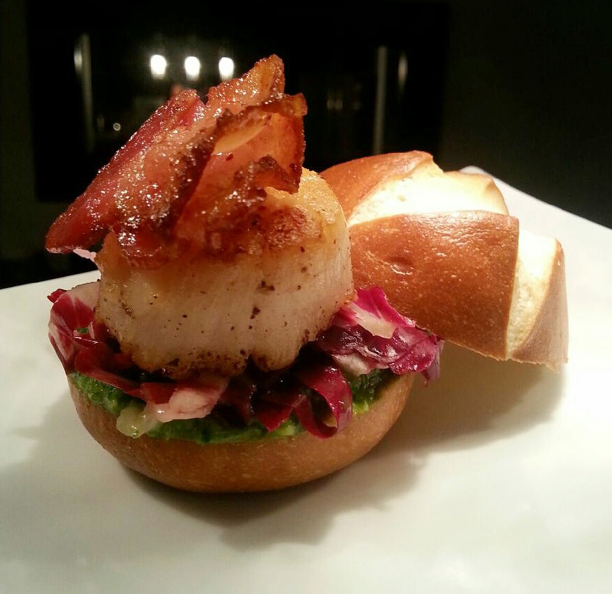 Pan-Seared Scallop Slider with a Radicchio Slaw and a Cilantro and Lime Sauce topped with Crispy Bacon..