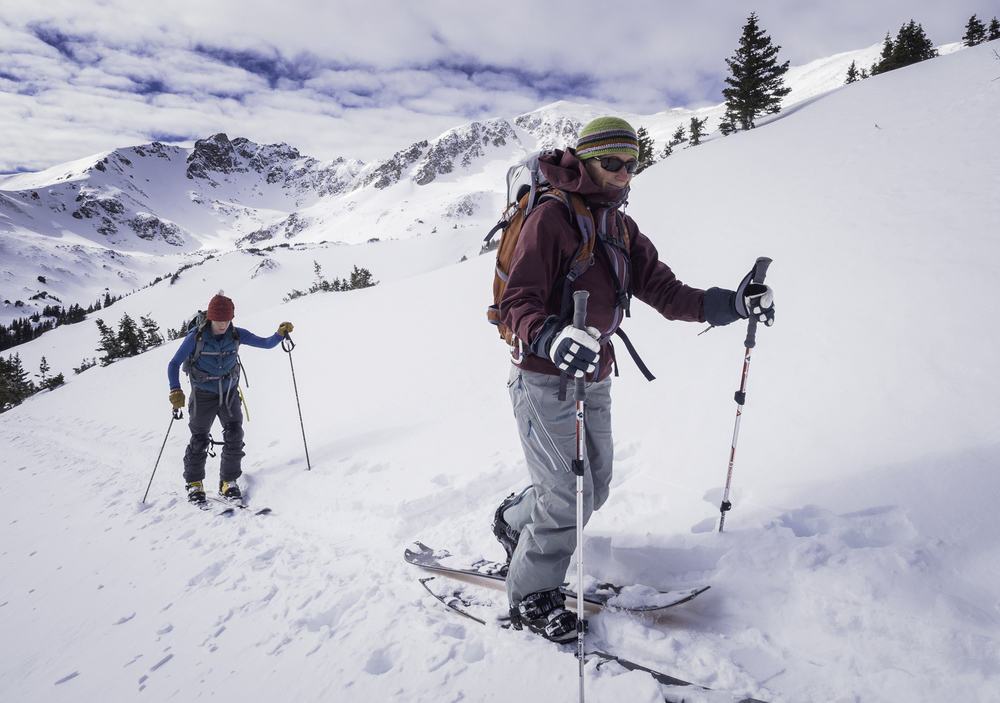 Heading to some SW facing terrain with the Herman Gulch Cirque behind - Colleen & Kristin