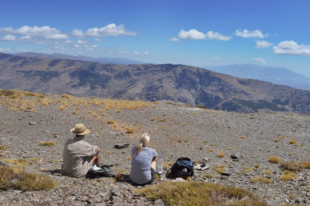 My partner Amanda and Jaime (from the fabulous  La Placeta  in Portugos, southern Spain) quietly sitting, looking over the many mountains  and out towards the coast of North Africa as part of our trek from Portugos to Trevelez.
