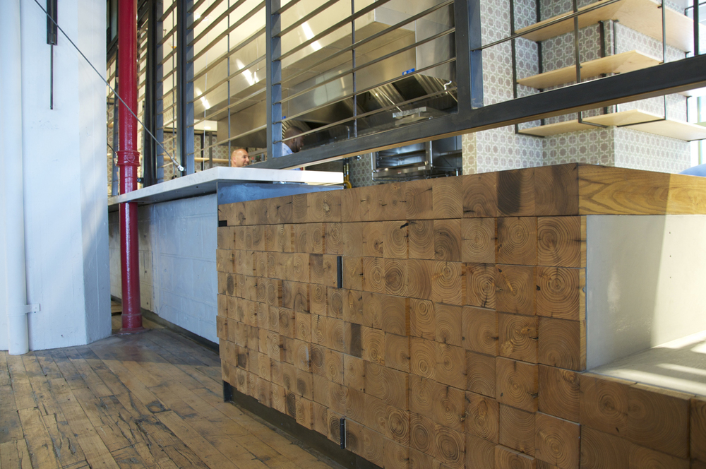 Cafe counter features reclaimed wood walls.
