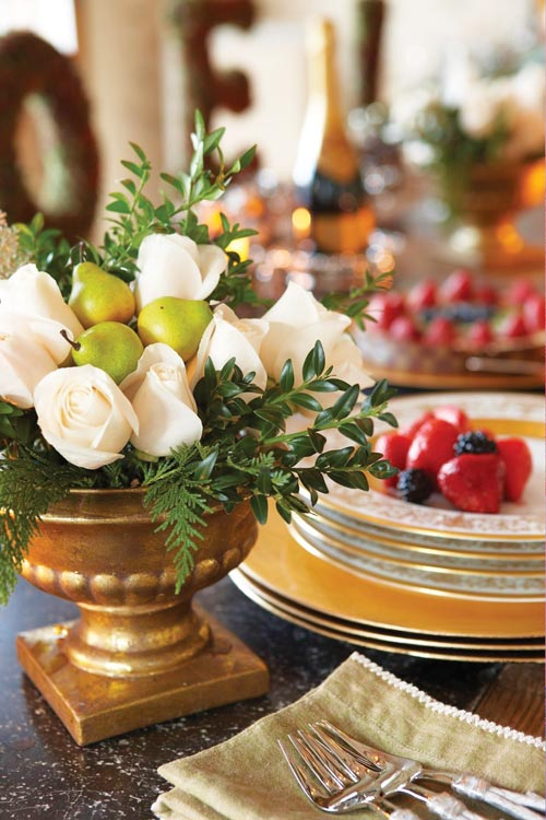 餐桌上,盤子裏色澤誘人的水果,金色容器中的白玫瑰、梨子和深綠色葉片的花藝令人賞心悅目。