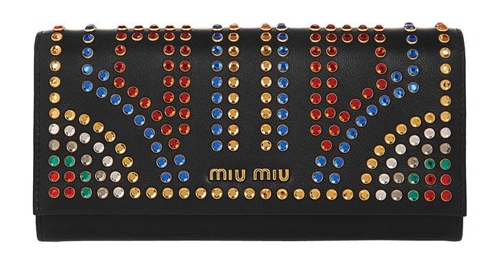 繆繆錢包 US$850 黑色的小牛皮上閃爍著霓虹燈般的五彩水晶和金色品牌標誌,內裏有實用的卡槽和帶拉鏈的零錢包。 Net-a-porter.com