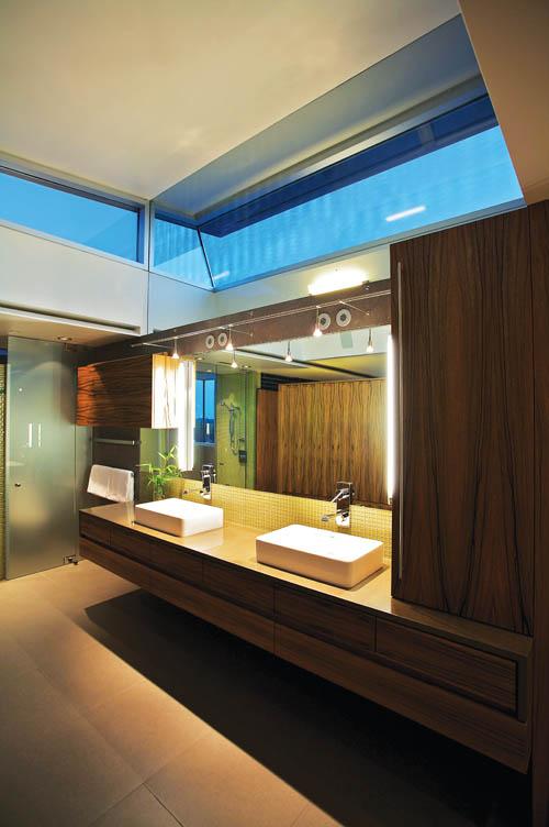 深色的木紋和淡綠色的瓷磚,讓浴室散發出幽靜的禪意,頂部還設有通透的天窗。