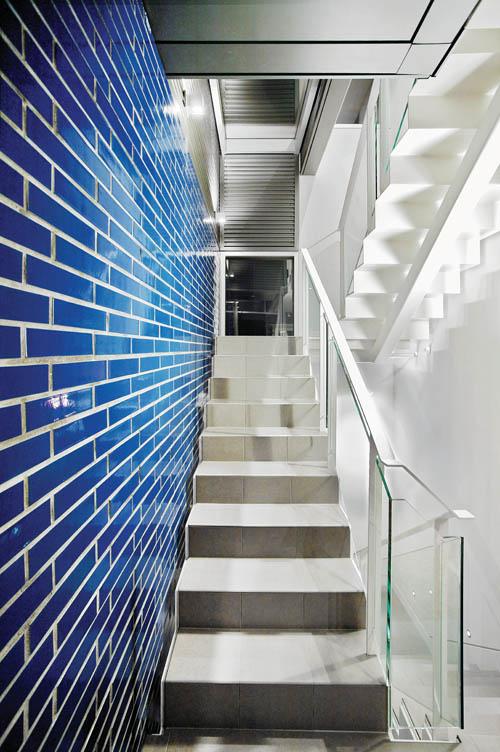 藍色的磚牆與灰色的金屬和臺階,以及通透的玻璃,共同營造出一條奇幻現代的走廊。