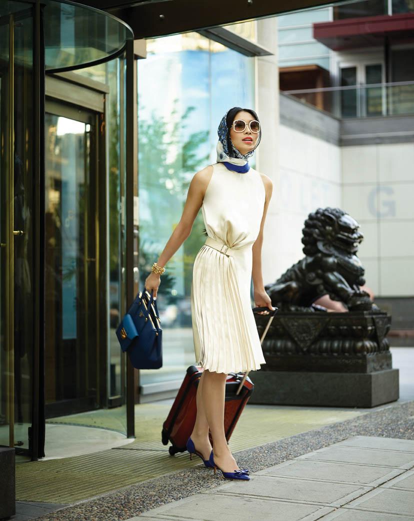 裙子($3,300)、高跟鞋、太陽鏡、絲巾,均來自菲拉格慕。普拉達藍色包包($2,665)來自Leone。Tumi行李箱($645)來自Holt Renfrew。 拍攝地點:溫哥華香格里拉酒店