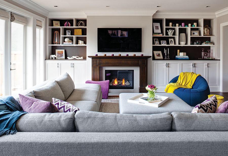 深色木質壁爐,定製置物架,灰色Salari地毯,跳色的沙發,營造出溫暖的家庭娛樂室。