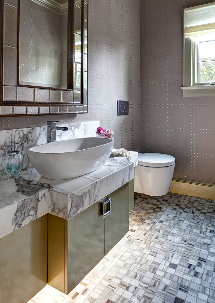 客用洗手間金屬質感的壁紙、裝飾鏡和櫥櫃,以及Victoria + Albert精緻的潔具。