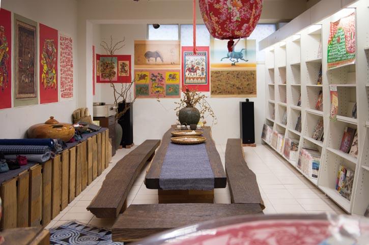「漢聲巷」內一角,天然的原木桌椅,牆上掛著《漢聲》出版的傳統年畫,古樸的擺設,聽著悅耳的古箏曲、一杯清香撲鼻的桂花烏龍,讓讀者在這裏悠閒地品茗閱讀。