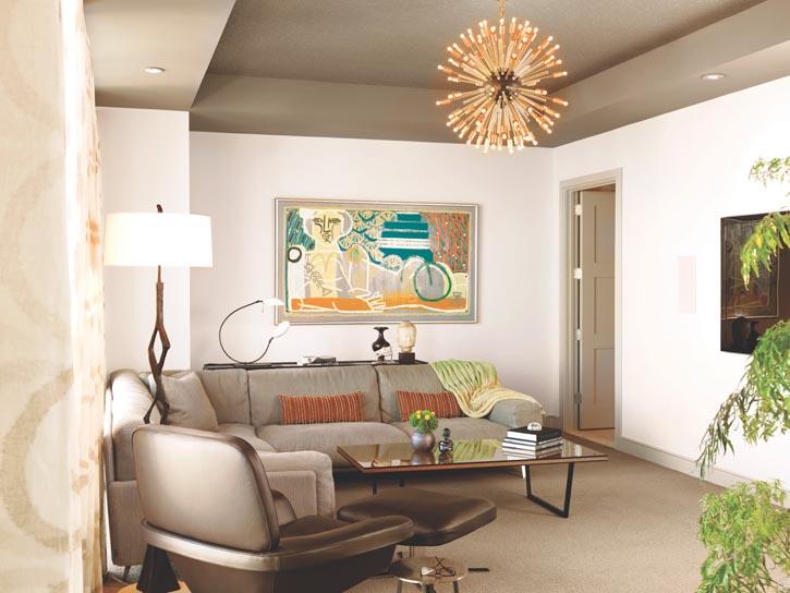 空間充足的轉角沙發,提供了舒適的觀影感受;橙綠色調的裝飾畫和綠色盆栽,為灰色調的空間增添了生機。