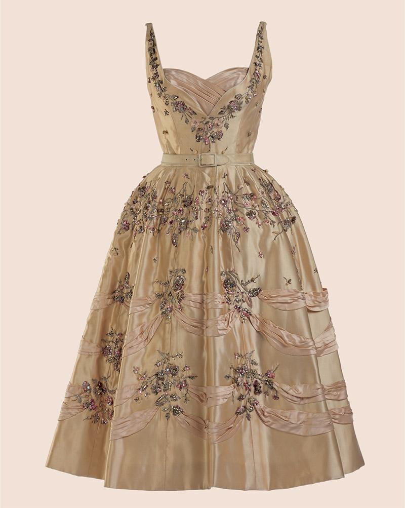 BALMAIN 1955 「漂亮夫人」流行模式 皮埃爾.巴爾曼(Pierre Balmain)在二戰後建立了他的品牌——「漂亮夫人」(Jolie Madame),他被譽為是最為客人著想的設計師。「漂亮夫人」所表現的高雅既不過於繁瑣,也不太過暴露。綢緞「Taglioni」晚禮服,內有襯裙,胸部和肩部的處理方式細膩地表現出女性特有的曲線。根據傳統做法,蓬蓬裙部份以繡花來突出禮服的嫵媚,散發著「北極光」的水晶、金線刺繡的花莖給亮麗的綢緞上添加了更多閃光點。