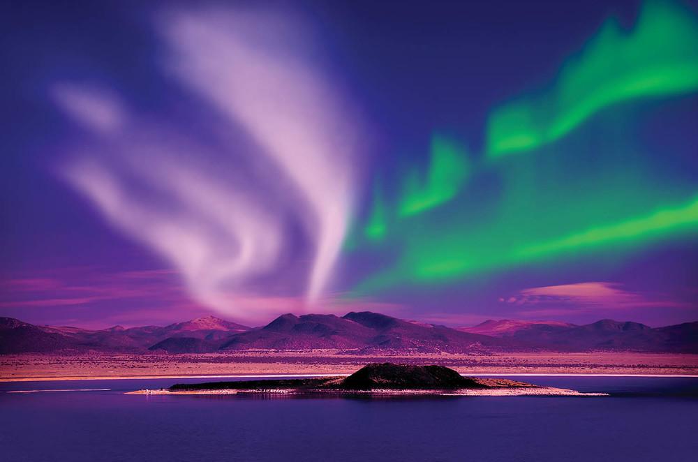 北極光超現實的顏色和光影閃耀在夜空中。(SurangaSL/shutterstock.com)