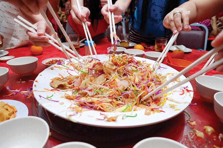 一家人對著裝滿魚生的大盤子,紛紛落下筷子使勁翻動的熱鬧場景。據說,從盤子裏掉出的菜餚越多,就意味著來年的生活會更富足。(Alexlky / Shutterstock.com)