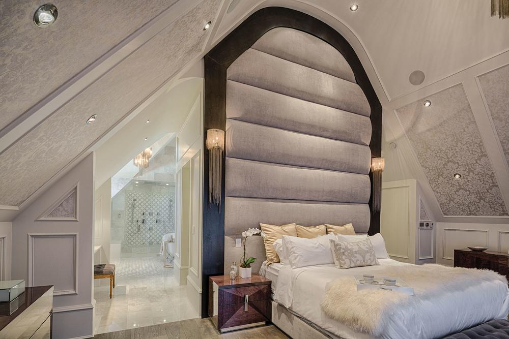 主臥內16呎高的天鵝絨軟包床頭,在兩側垂落的水晶壁燈的映照下盡顯奢華。浴室為開放式設計,地面鋪設白色大理石。