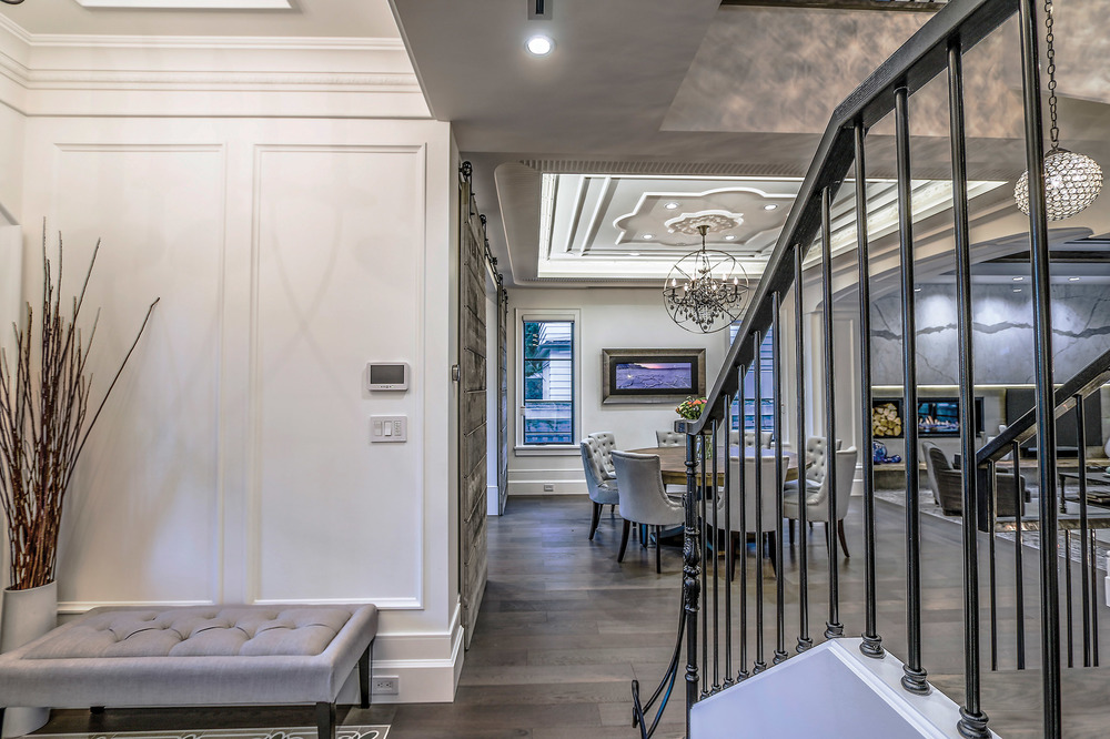 從門廳處可以看到正式餐廳那華麗精美的吊頂,與深灰色的鐵皮拉門形成有趣的對比。鐵藝的黑色樓梯欄杆有著精緻的法式風格,與深灰色的木地板相互呼應。