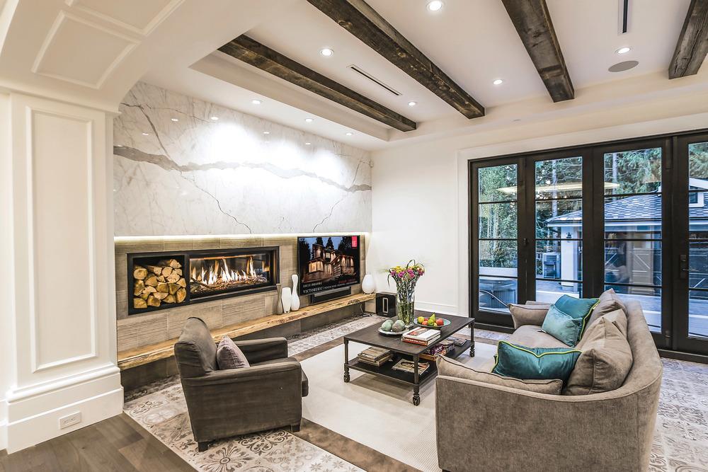 舒適的客廳兼家庭休息室,屋頂上裝飾著來自俄勒岡州一個舊穀倉的木質橫樑,牆壁被製作得斑駁開裂,Statuario大理石裝飾的壁爐正在熊熊燃燒。