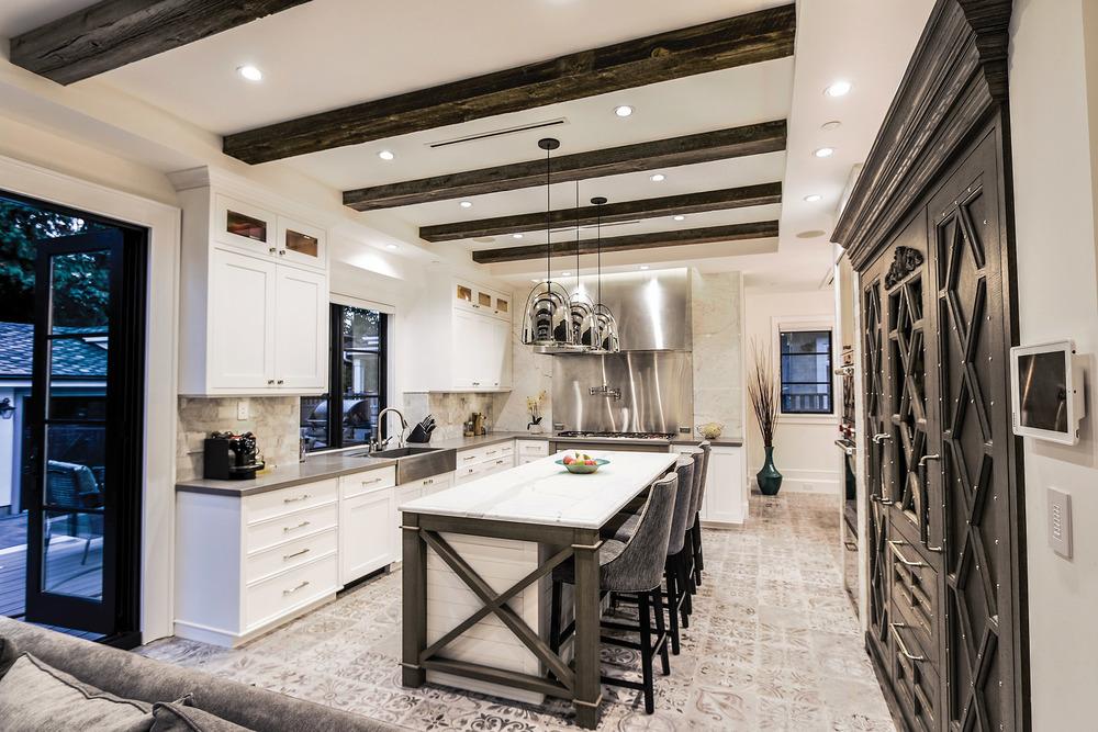 設計靈感來自法式咖啡廳,廚房的中央島臺覆蓋著白色大理石檯面,下方用深灰色的木材打造出框架支撐。裝飾著鉚釘的法式櫥櫃之內有酒櫃等現代電器。