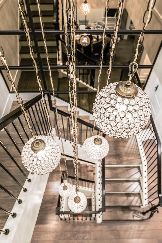 樓梯井內的球形水晶吊燈懸掛在金屬鐵鏈上,從二樓垂落至一樓。
