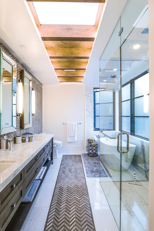 浴室內用灰色的大理石在地面和牆面上鑲嵌出傳統的人字形圖案,檯面為白色大理石,天花板則延續了一樓的木質橫樑。施華洛世奇水晶吊燈閃耀在浴缸的上方。