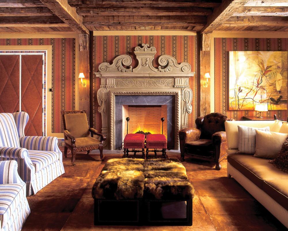 屬於一家人溫習歡聚的家庭房,原木打造的天花板橫樑裝飾與皮毛的矮桌格外質樸溫暖,華麗的壁爐則延續了客廳和餐廳的古典裝飾風格。